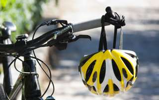 a bicycle helmet hanging from the handlebars