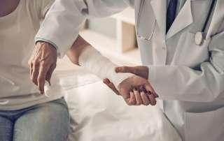 Doctor bandaging woman's injured arm