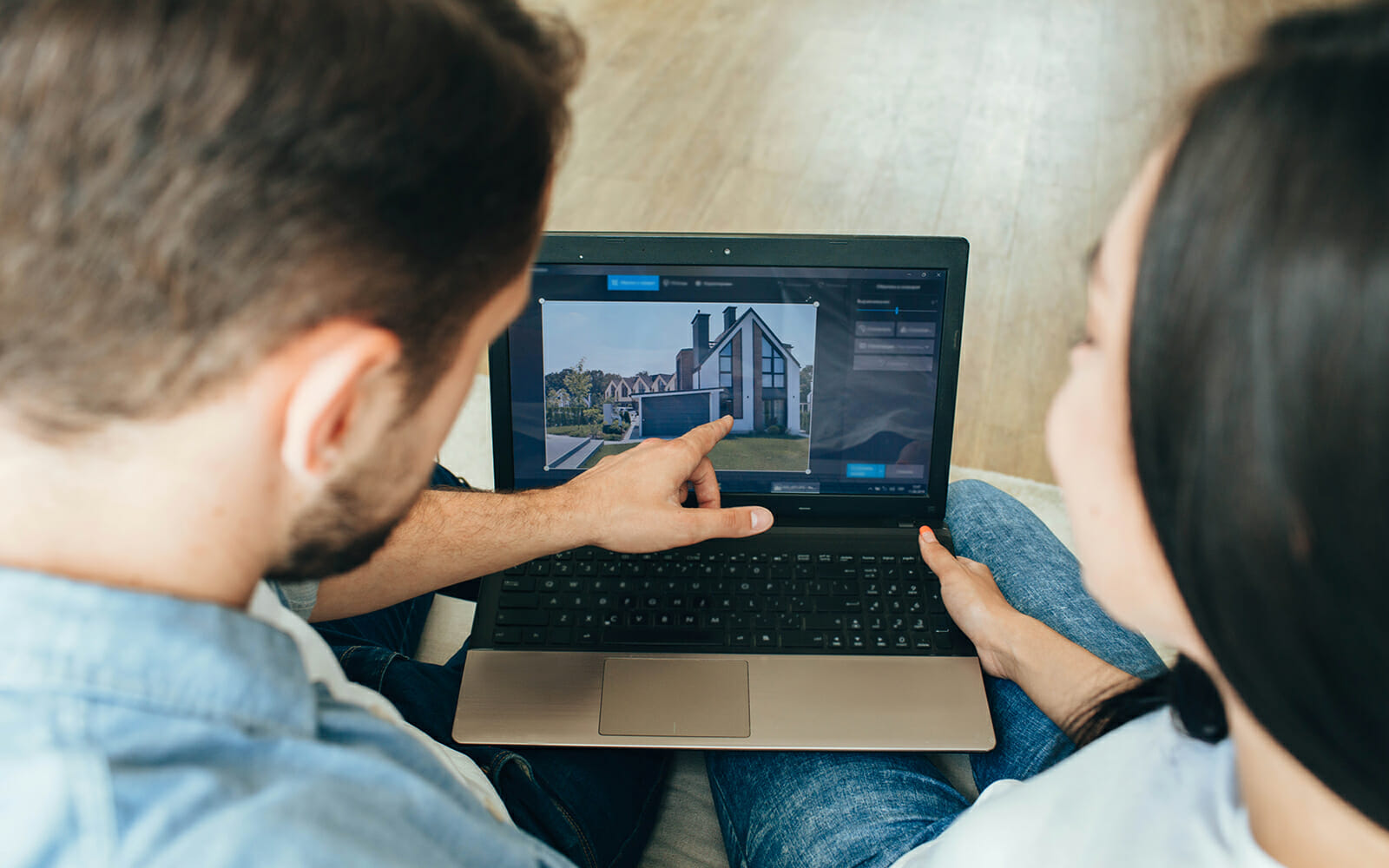 A couple looking at potential houses on a laptop